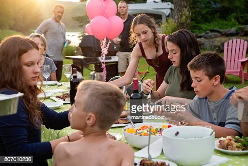 Big family barbecue gathering at sunset, summer outdoors. : Stock Photo