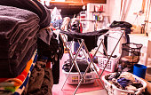 An authentic home basement laundry utility room overflowing on laundry day with heaps of dirty and clean laundry. The household washing maching and dryer are working overtime - a full day housekeeping