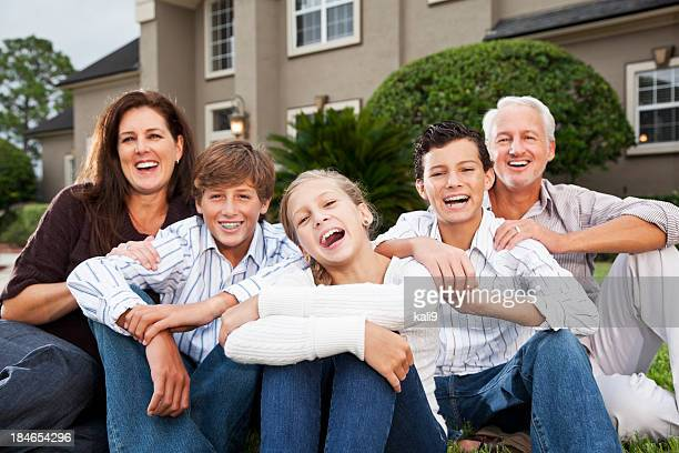 Big family sitting outside house