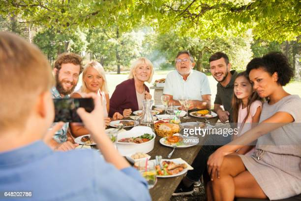 Big family taking portrait photo at picnic