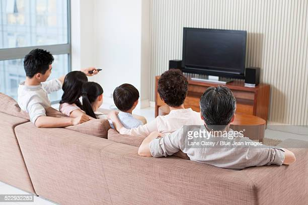 Big family watching TV in living room