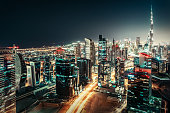 Fantastic nightime skyline: big futuristic city with illuminated world tallest skyscrapers. Dubai downtown, United Arab Emirates. Colorful travel and architectural background.