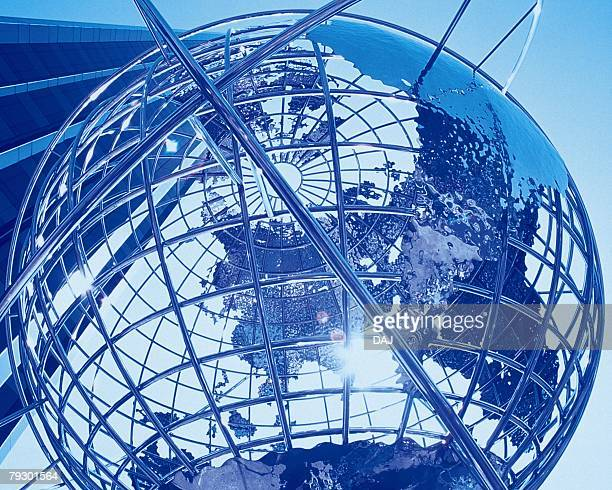 Big globe in front of high-rise building, low angle view, close up, toned image