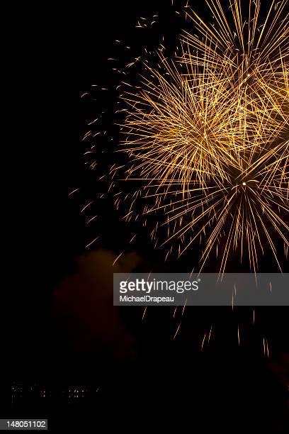 Big oro fuegos artificiales en el cielo de un lago