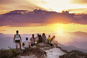 Big group of friends stands on mountain top and looks at beautiful sunset. Travel with friends concept