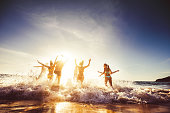 Big group of friends runs in sun light at the beach into the sea. Travel concept. Space for text