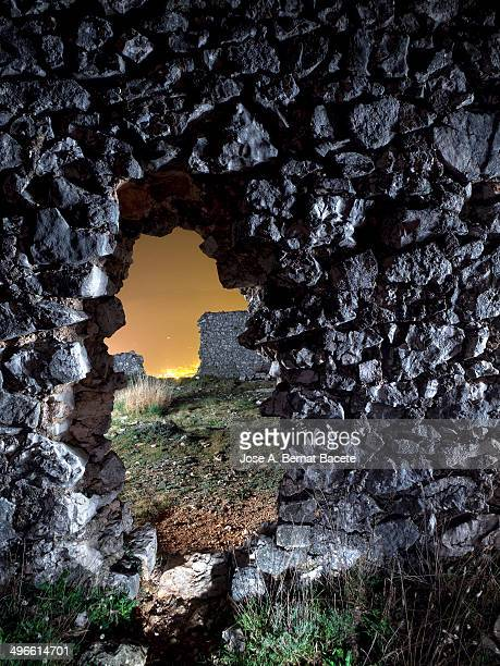 Big hole in a stone wall of an old corral at night