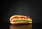 Big hotdog with sausage tomatoes, mustard and salad isolated on black background. Top view.