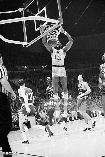 INGLEWOOD CA Big LA Laker center Wilt Chamberlain jumps to the rim of the basket to score as Boston Celtics Tom sanders forward and Larry Siegried...
