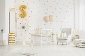 Three big pink lampshades hanging above bed for baby in bedroom with dotted wall