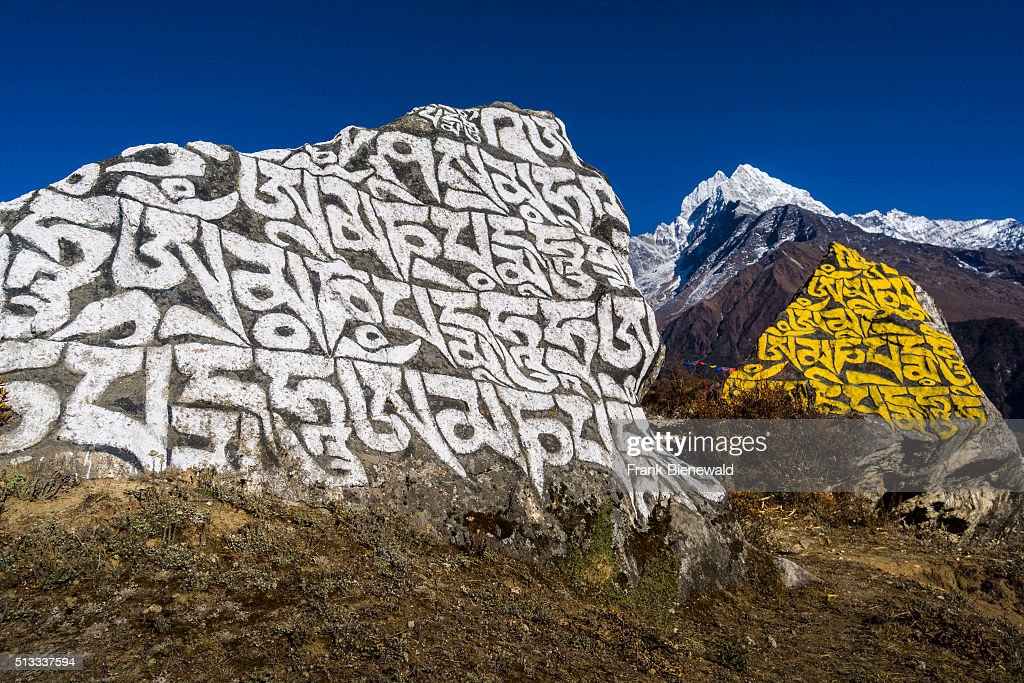Big Mani stone with the tibetean mantra Om mani padme hum with the mountain Kangtega in the distance