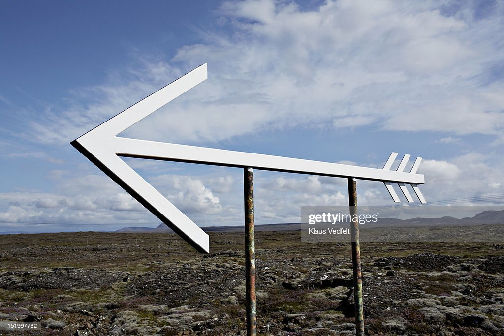 Big metal arrow sign in lava landscape : Stock Photo