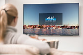 Big modern TV with 4k resolutions and young woman on foreground watching some video