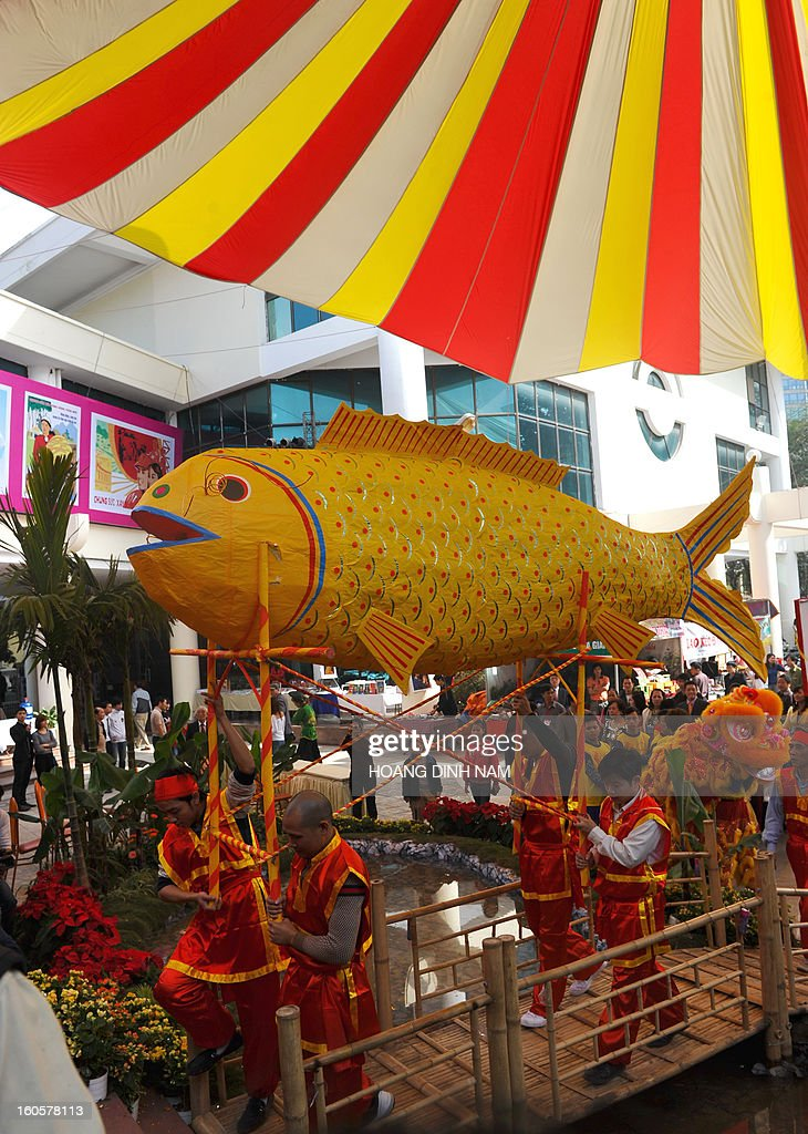 A big paper-made carp is carried during a procession to mark the 'Kitchen God Day', part of Lunar New Year or Tet celebrations by Vietnamese, in dowtown Hanoi on February 3, 2013. Vietnamese believe that Tet marks the time when the Kitchen God reports on their family to the Jade Emperor on the 23rd day of the 12th lunar month, meaning a week before Tet. On that day families usually burn gold leaf paper and offer live carp for him to ride. AFP PHOTO / HOANG DINH Nam