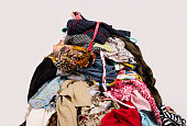 Untidy cluttered wardrobe with colorful clothes and accessories on the ground.