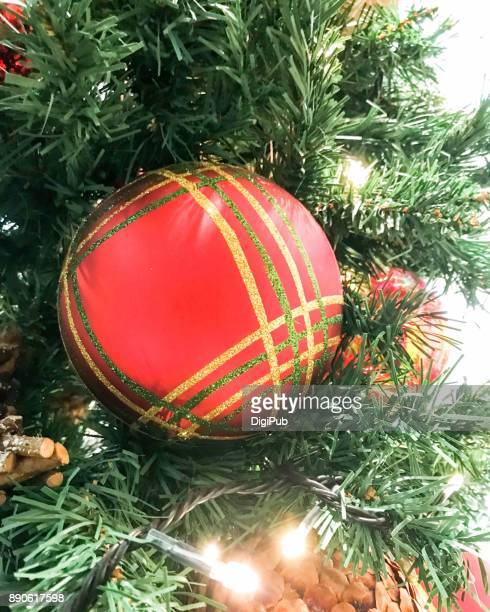 Big red bauble hanging in artificial Christmas tree