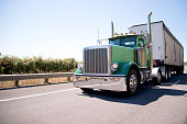 Classic American bonneted large green rig semi truck with high stylish chrome exhaust pipes transporting commercial cargo in bulk container trailer on the highway with trees behind the safety fence