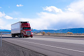 Big rig American bonnet powerful red semi truck with refrigerated semi trailer with refrigerator unit for cooling trailer inside space transporting commercial cargo on flat road in Utah