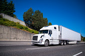 White modern Big rig semi truck with reefer semi trailer equipped with refrigeration unit going on flat wide highway with commercial cargo for delivery to warehouse