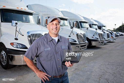 Big rig trucks behind man holding tablet
