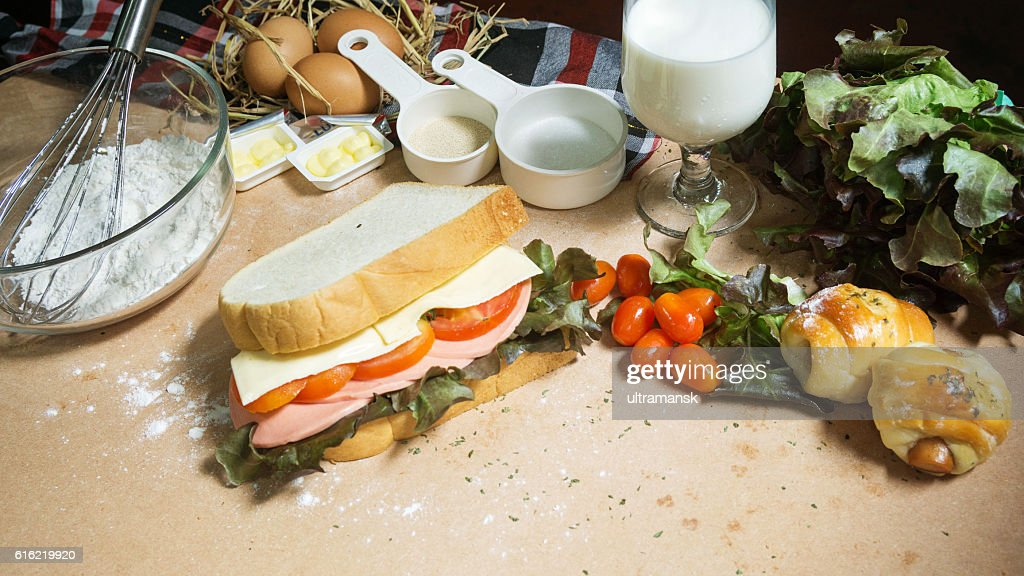 big sandwich with ham, cheese and vegetables on woodboard : Stock Photo