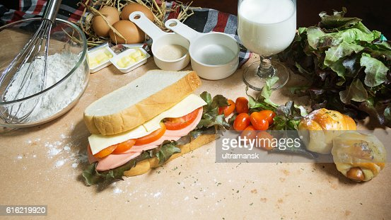 big sandwich with ham, cheese and vegetables on woodboard : Bildbanksbilder