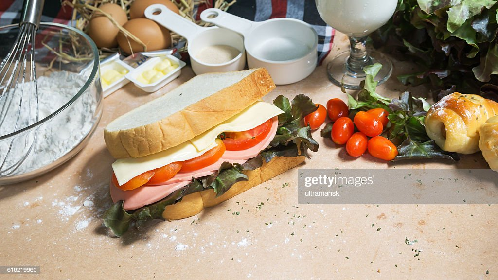 big sandwich with ham, cheese and vegetables on woodboard : Stockfoto