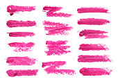 Big set of fuchsia lipstick smudge isolated on white background. Smudged makeup product sample
