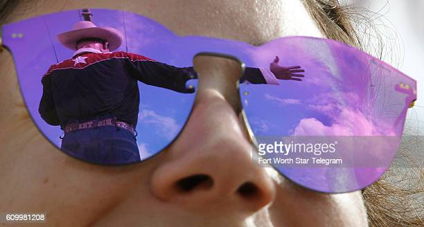 Big Tex is reflected in Simone Elices' sunglasses with the State Fair of Texas one week away as crews put up the iconic statue at the north end of...