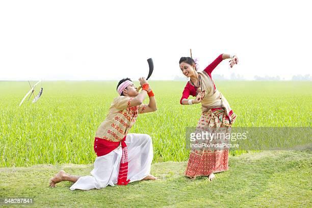 Bihu man blowing on a pepa while Bihu woman dances to his tune