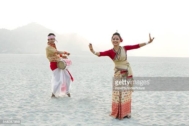 Bihu woman dancing as Bihu man plays on a dhol