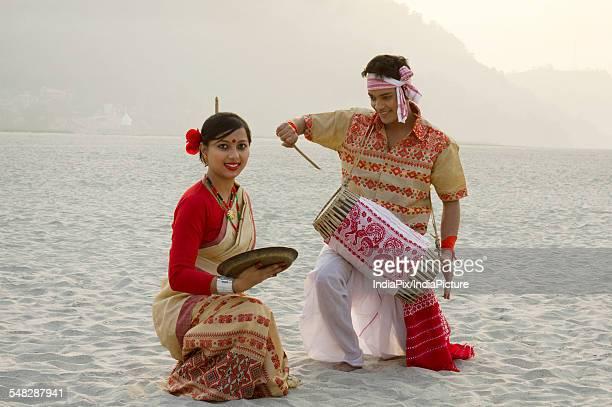 Bihu woman dancing with a brass plate as Bihu man plays on a dhol