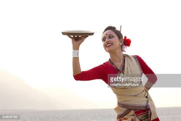 Bihu woman dancing with a brass plate