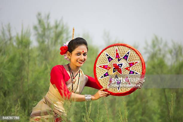 Bihu woman holding a jaapi