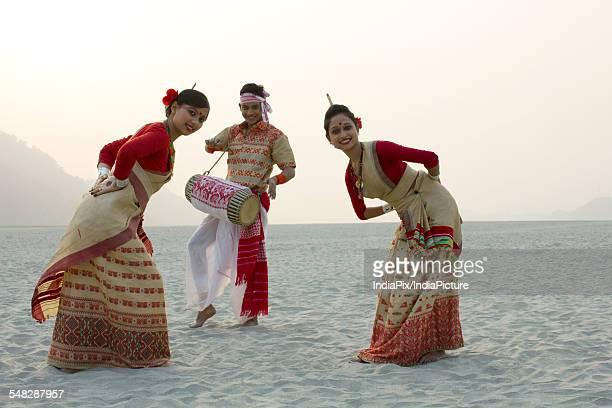 Bihu women dancing as Bihu man plays on a dhol