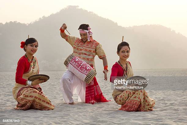 Bihu women dancing with brass plates as Bihu man plays on a dhol