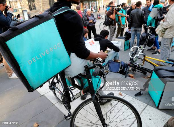 Bike delivery people from the Deliveroo food delivery service gather for a demonstration on August 11 2017 at Place de la Republique in Paris...