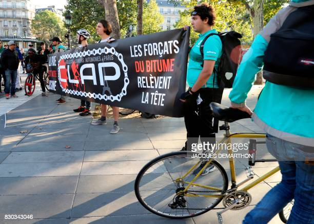 Bike delivery people from the Deliveroo food delivery service hold banners during a demonstration on August 11 2017 at Place de la Republique in...