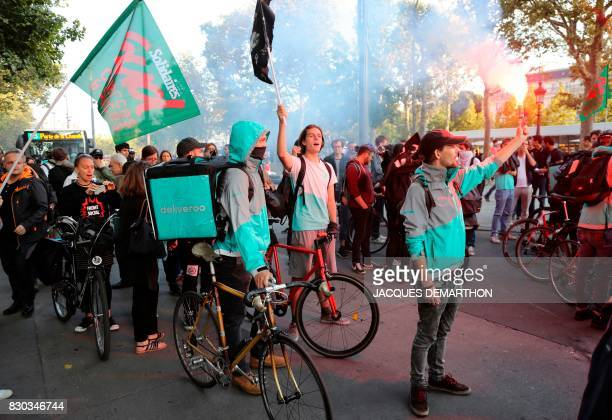 Bike delivery people from the Deliveroo food delivery service wave flares and flags during a demonstration on August 11 2017 at Place de la...