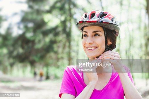 Bike helmet. Woman Putting Biking Helmet on Outside During Bicycle Ride. : Stock Photo