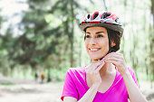Woman Putting Biking Helmet on Outside During Bicycle Ride.