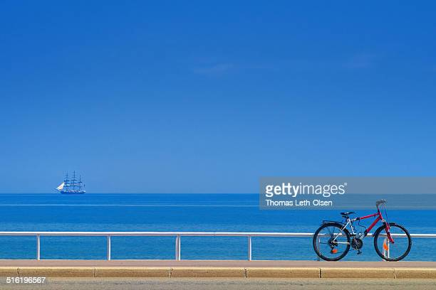Bike in front of blue sea, ship in distance