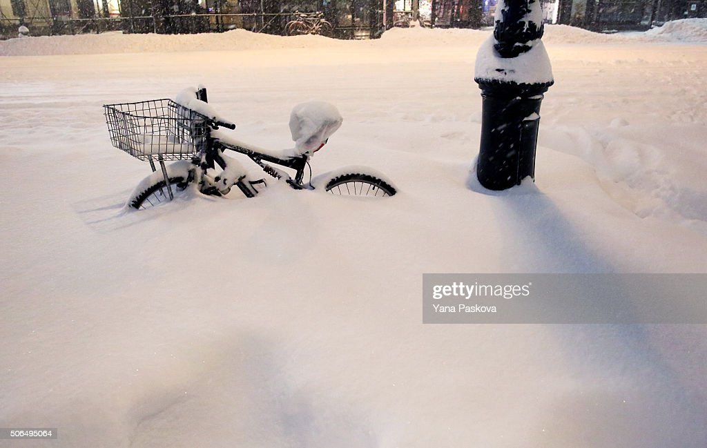 A bike is buried near Bryant Park as all cars but emergency vehicles are banned from driving on the road on January 23 2016 in New York City The...