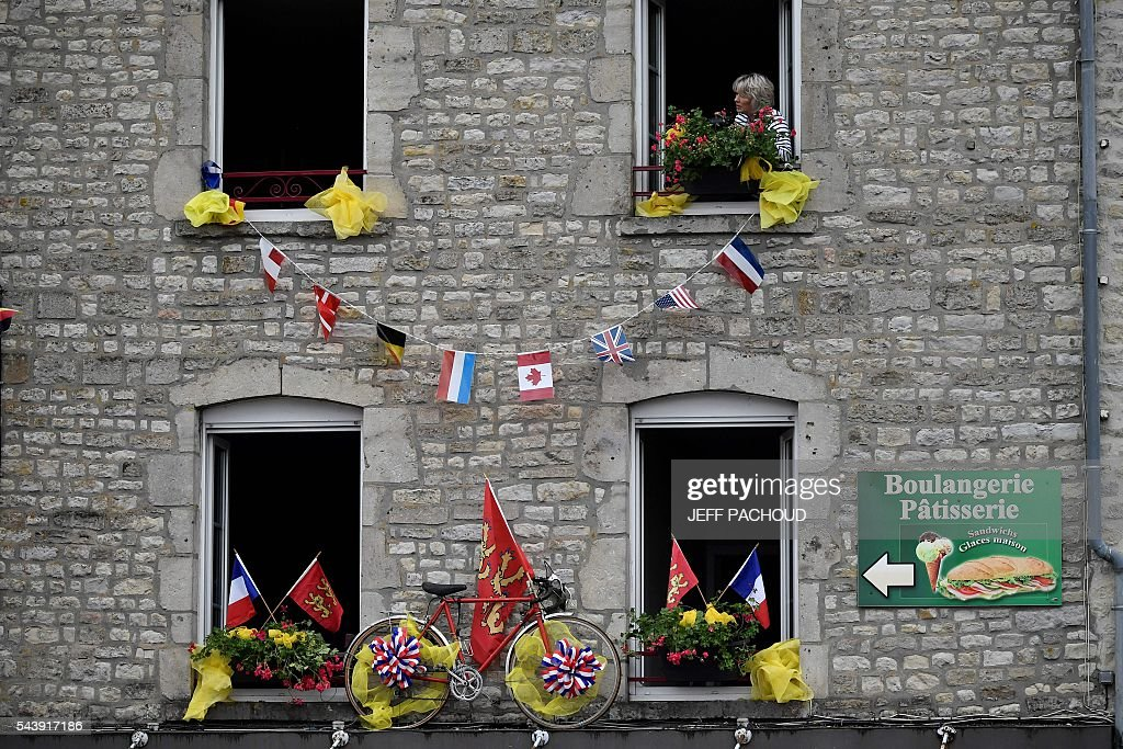 A bike is installed on the facade of an apartements building as a woman looks out from her window in Sainte-Marie-du-Mont, Normandy, on July 30, 2016, two days before the start of the 103rd edition of the Tour de France cycling race. The 2016 Tour de France will start on July 2 in the streets of Le Mont-Saint-Michel and ends on July 24, 2016 down the Champs-Elysees in Paris. / AFP / jeff pachoud