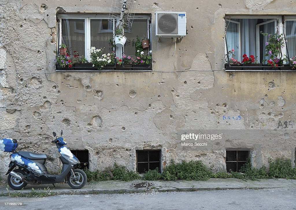 A bike is parked in front of a concrete wall damaged by bulletts from the 1993 war as the city of Mostar remembers the 1993 conflict on June 28, 2013 in Mostar, Bosnia and Herzegovina. The Siege of Mostar peaked in 1993 during the Croat-Bosniak conflict lasting eighteen months as fighting took place as Bosnia and Herzegovina declared independence from Yugoslavia. The city was divided in half between the two battling armies. Mostar, dating back over four hundred years, was mostly destroyed through the fighting. Although reconstruction has slowly commenced in the last decades, evidence of the war remains in bullet ravaged buildings still standing throughout the city.