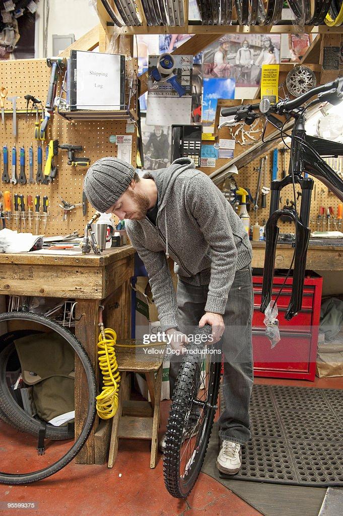 Bike mechanic working on bike in shop : Stock Photo
