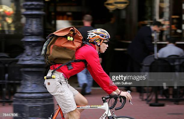 A bike messenger carries a package as he rides down Market Street July 17 2007 in San Francisco California With courts using electronic filing to...