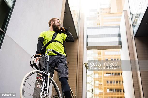 Bike Messenger Communicating With Walkie Talkie