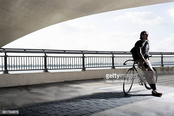 Bike messenger leaning on bike