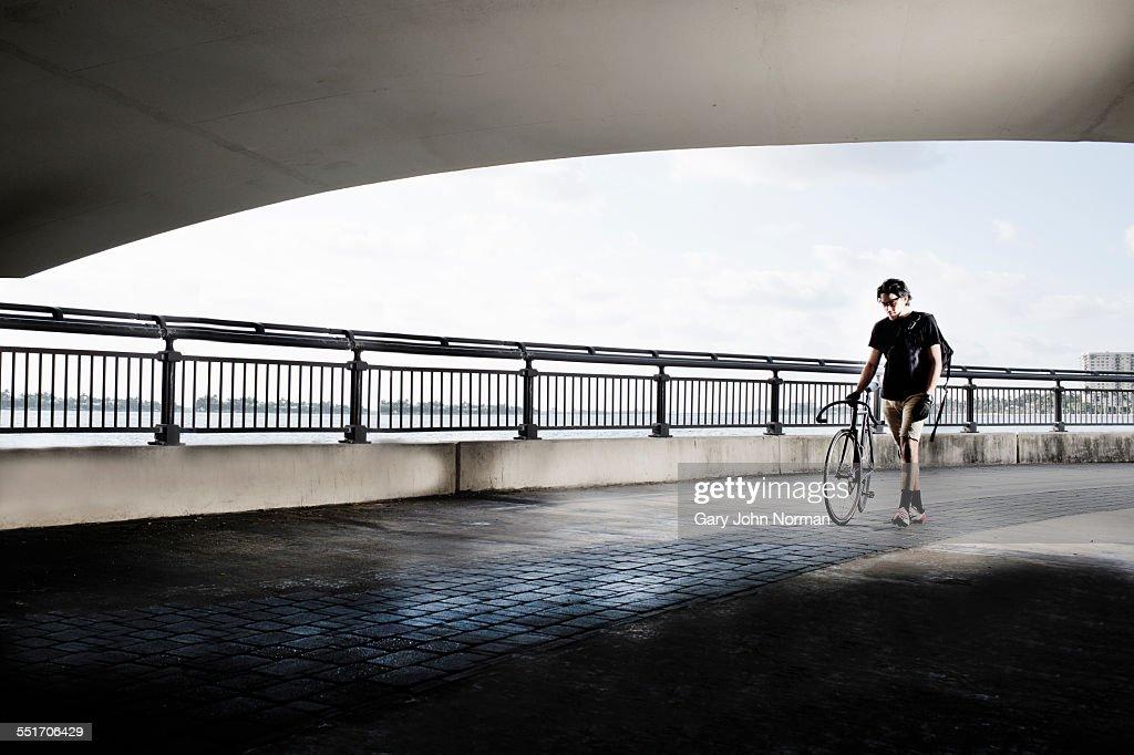 Bike messenger walking, pushing bike